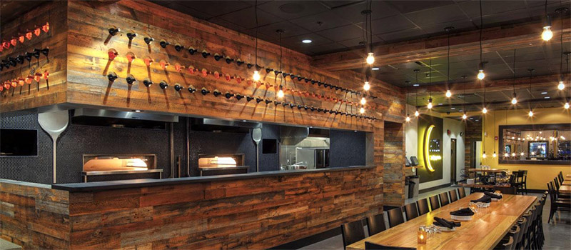 Rustic wood paneling adds warmth in pizza restaurant
