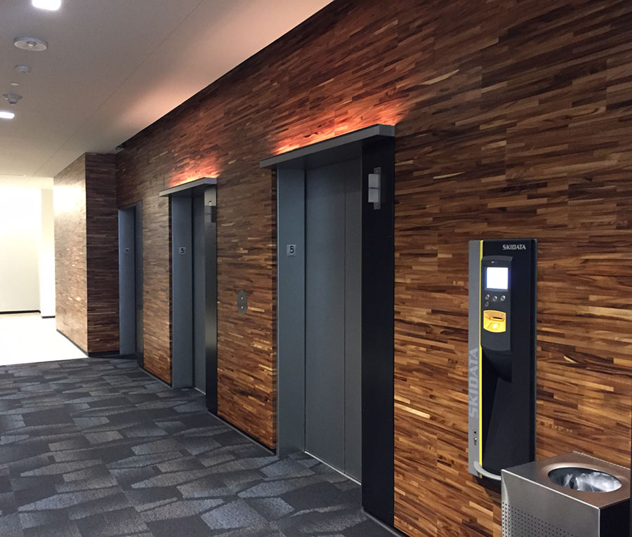 Post-industrial reclaimed acacia is used as wall paneling in elevator lobby