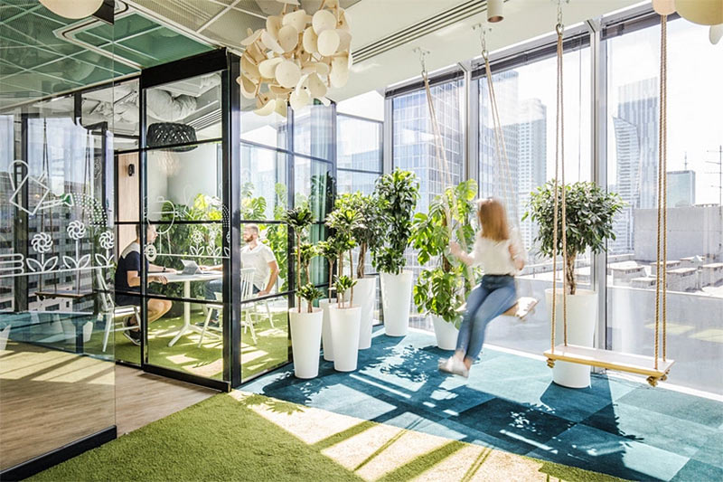Allegro Office with plants, large windows, and swings