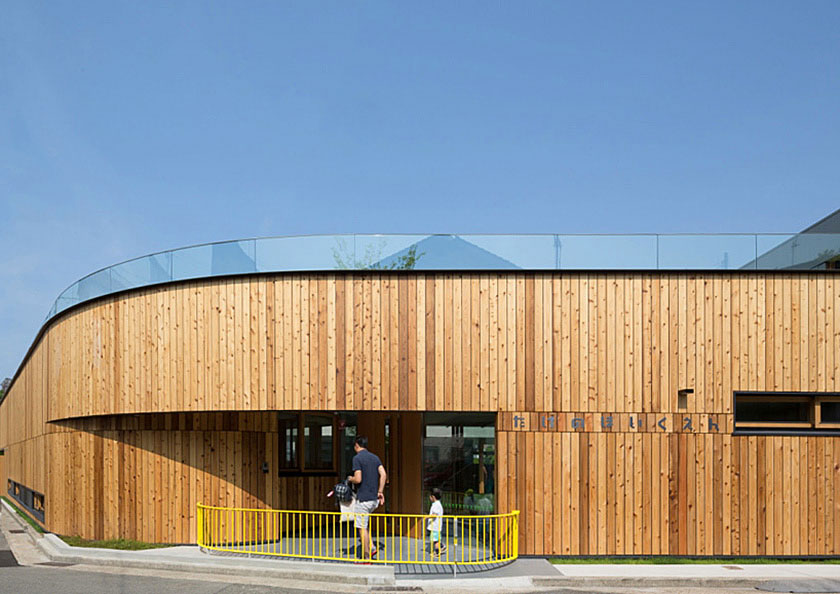 Vertical Cedar siding accentuates building's geometry at child nursery in Japan
