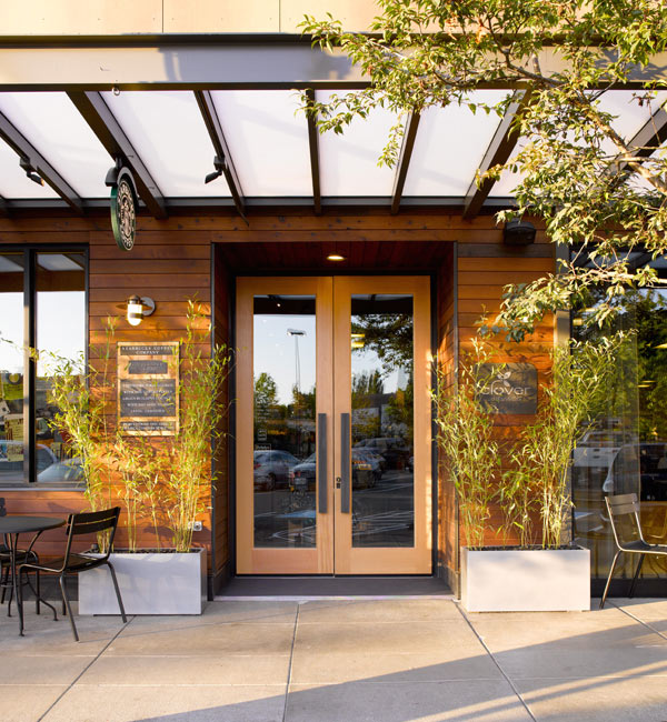 Reclaimed wood paneling complements potted greenery and trees outside this Seattle Starbucks